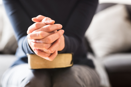 Bible study and Christian faith concept - closeup shot of a woman holding her hands together and praying with a Bible in her lap. Stockfoto
