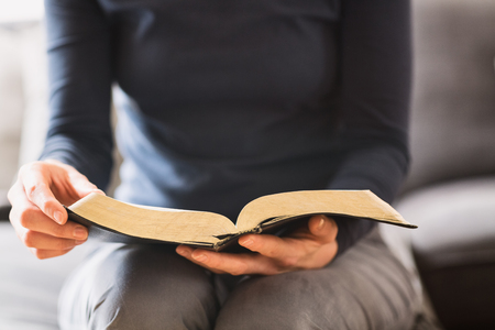 Closeup shot of a woman holding an open Bible and reading from it. Stockfoto