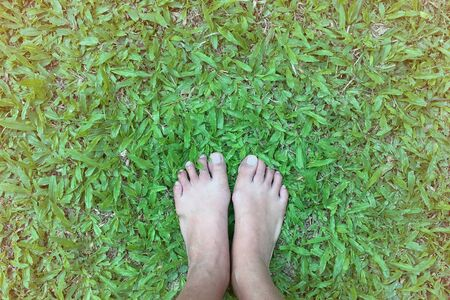 Asian woman bare foot standing on green grass for relaxation