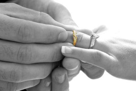 groom places ring on brides finger Standard-Bild