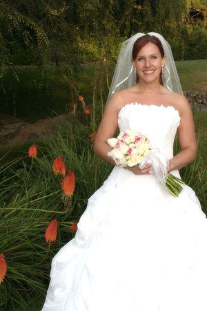 bride poses by orange flowers