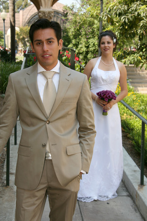 groom poses while bride is in the background
