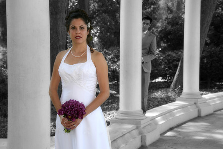 bride poses while groom is in the background