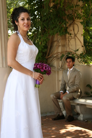 bride poses for a photo while groom sits in the background Standard-Bild