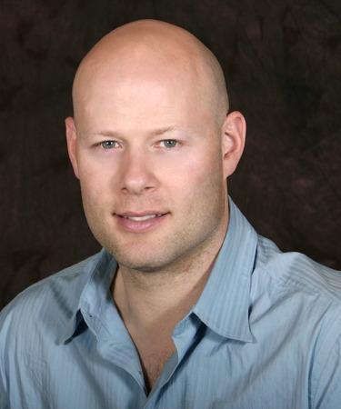 head shot of a young goodlooking bald man