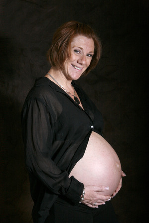 mom smiles while she shows off her pregnant belly