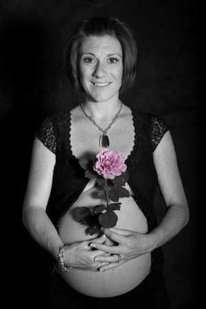 mom holds a flower over her pregnant belly