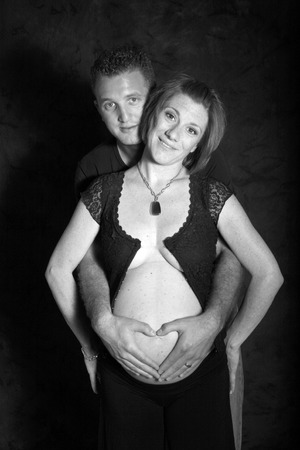 dad places a heart over moms pregnant belly Standard-Bild