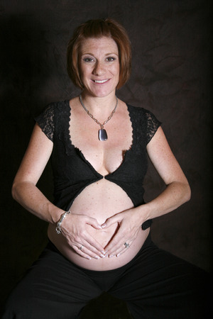 mom places a heart over her pregnant belly