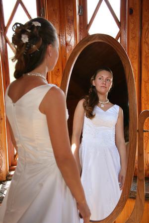 bride looks into a mirror