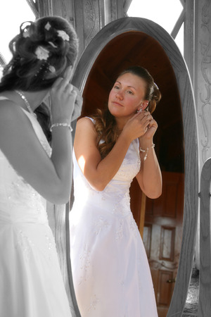 bride puts on her ear rings while looking in mirror