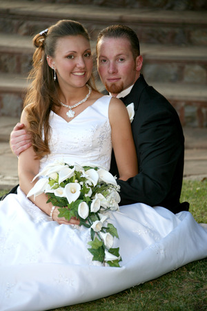 bride and groom sit on the grass