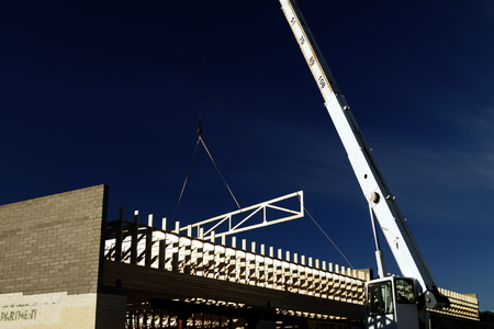 configurations: 4x2 roof truss with chase lifted by telescopic boom crane, hovering over building as it is being installed