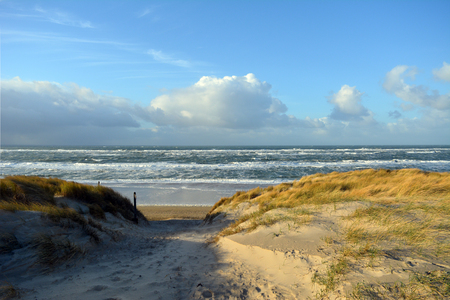 Uitzicht tussen twee duinen, geteeld met strandgras, op een Noordzeestrand op Texel. Eiland in Holland.