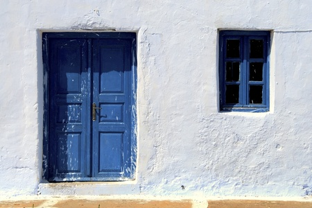 peeling paint: The old Greek houses with blue doors and windows Stock Photo