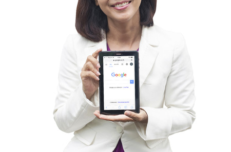 media gadget: THAILAND, BKK - JUNE 17: Asian businesswoman holding a tablet on white background at 17 June 2016