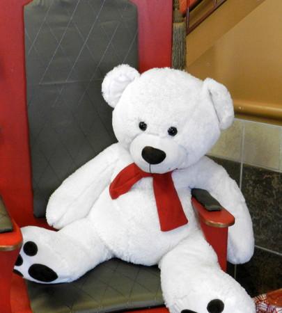 White teddy bear sitting on a chair