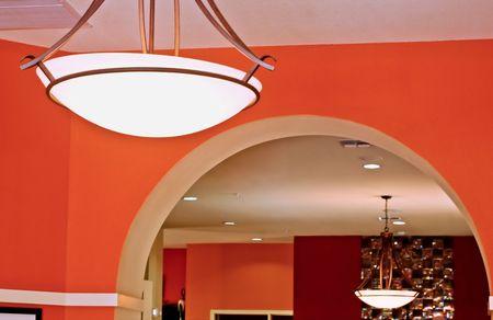 Una puerta de arco separa dos habitaciones con chandliers dentro de una casa con paredes de color brillante.  Foto de archivo - 7795341