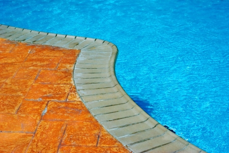 edge: A curved line of an outdoor pool separates the beautiful blue water and the orange tiles and beige-color edges on the ground.
