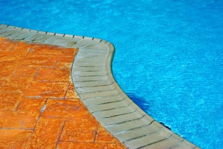 geschwungene linie: Eine gekr�mmte Linie von einem Au�enpool trennt die sch�nen blauen Wasser und die orange Fliesen Beige-Color Kanten auf dem Boden.