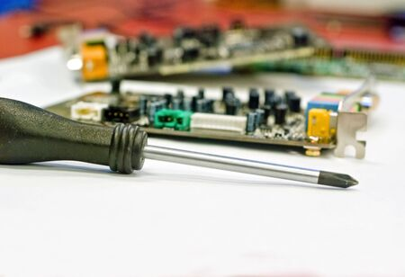 A screwdriver in front of some disassembled circuit board of a computer. Stok Fotoğraf