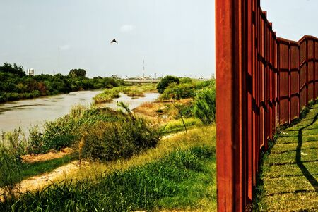 defines: A metal border wall running parallel to a path near Rio Grande which defines the national border of US and Mexico.
