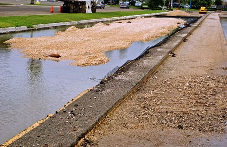 A view of a divided road under construction after rain.  Pool water from the rain and gravels on one side.  A narrow paved section run throgh the picture.