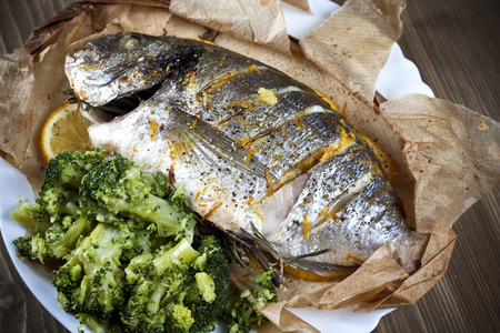 fish dinner: Baked dorado with oranges and rosemary Stock Photo