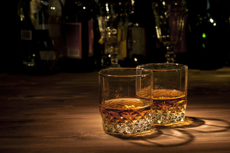 bar: Two glasses of whiskey on a wooden table in the bar Stock Photo