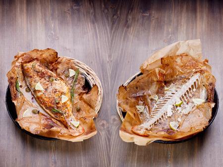 alcaparras: Pescado cocinado en papel bakng y una espina de pescado