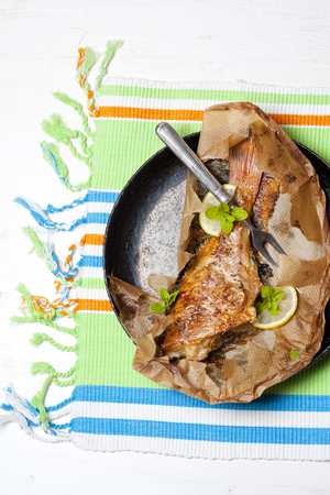 Rockfish baked in paper on a white table Stok Fotoğraf