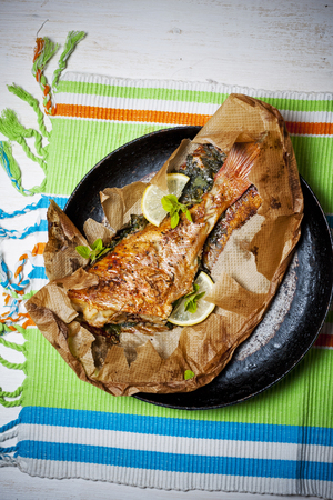 redfish: Rockfish baked in paper on a white table Stock Photo