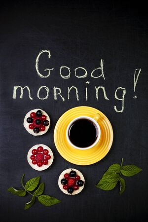 Cup of coffee with three cakes on a black background and a good morning text Stok Fotoğraf