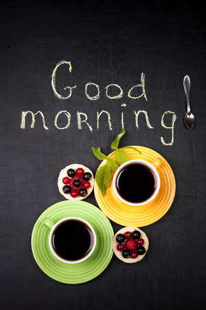Two cup of coffee with two cakes on a black background and a good morning text