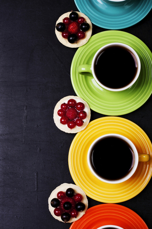 Cups of coffee with three cakes on a black background Stok Fotoğraf