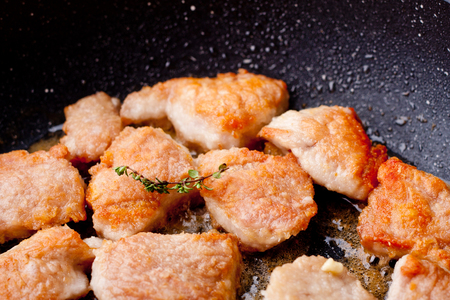 Pieces of turkey being fried on a pan