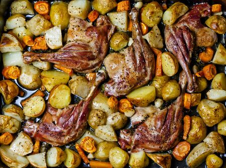 Baked duck legs with vegetables and potherbs