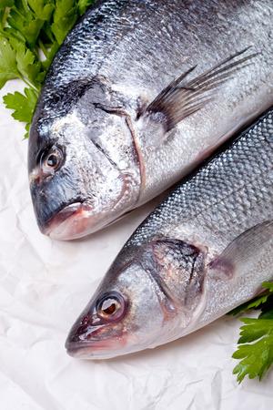 Raw dorado and sea bass on a kitchen table