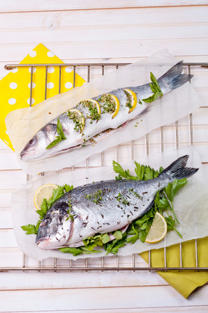 Dorado and sea bass on a kitchen table ready to be cooked