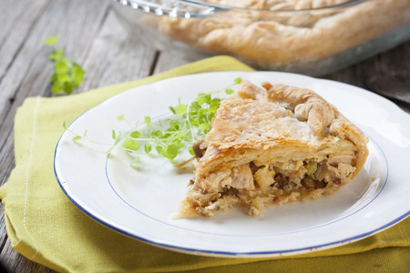 Puff pastry pie with fowl and leek filling on an old wooden table