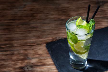 A glass of mojito cocktail on a slate (black stone) coaster.