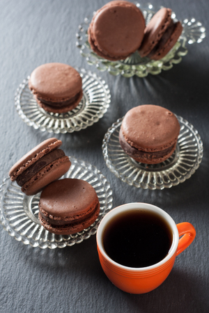 Chocolate macaroons and a cup of coffee on a natural stone surface Stok Fotoğraf