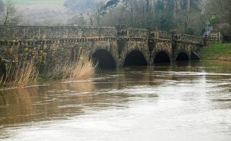 An old stone bridge across a river