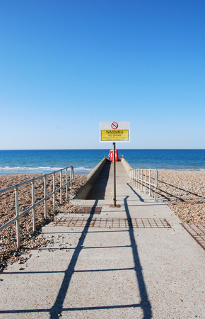 no diving sign: A concrete walkway extending across a pebble beach towards the sea.. Seen under a cloudless blue sky with a blue sea beyond. The walkway is lined with safety rails and has a no diving warning sign and a lifebuoy at the seaward end. A shadow of the safet Stock Photo