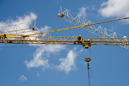 slings: Booms of tower cranes on a background of blue sky