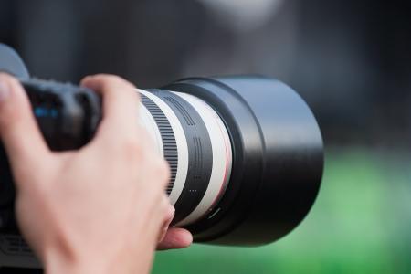 telephoto: Camera with pro-grade telephoto lens in photographer Stock Photo