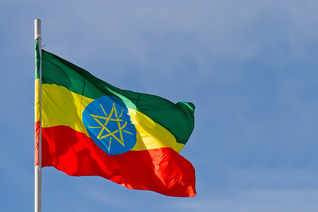 Ethiopia flag is waving in front of blue sky photo