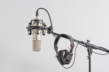 condenser: Professional condenser microphone with headphones on a stand. White background.