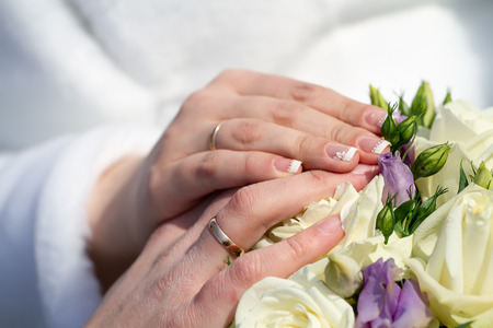 Hands of just married with golden rings.