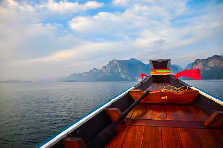 Wooden boat in the lake with beautiful sky and mountains